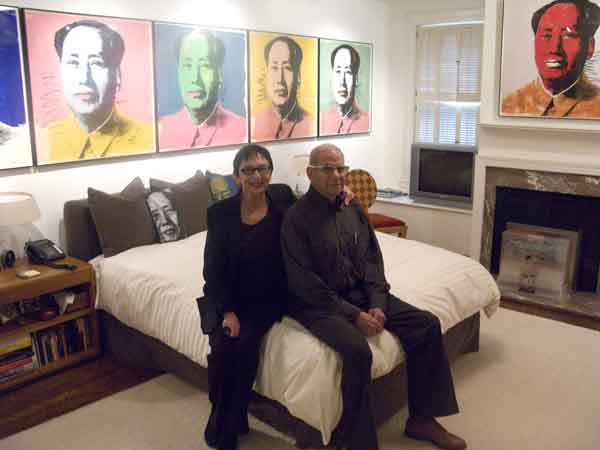"The Levines in their bedroom, lined with Warhol ""Mao"" prints."